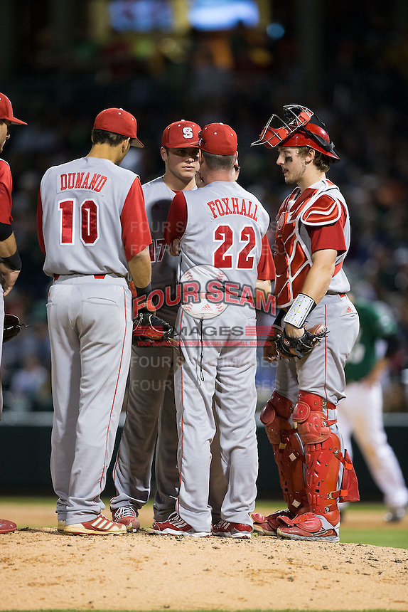 North Carolina State Wolfpack assistant coach Scott Foxhall (22) has a meting on the mound with relief pitcher Jon Olczak (17) as third baseman Joe Dunand (10) and catcher Andrew Knizner (11) look on during the game against the Charlotte 49ers at BB&T Ballpark on March 31, 2015 in Charlotte, North Carolina.  The Wolfpack defeated the 49ers 10-6.  (Brian Westerholt/Four Seam Images)