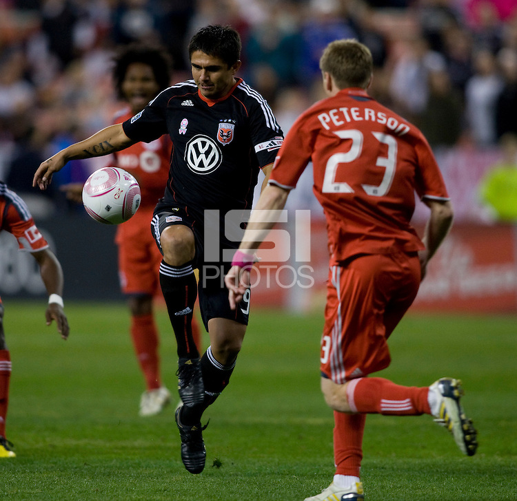 Jaime Moreno (99) of D.C. United passes the ball away from Jacob Peterson (23) of Toronto FC during the game at RFK Stadium in Washington, DC.  Toronto defeated D.C. United, 3-2.
