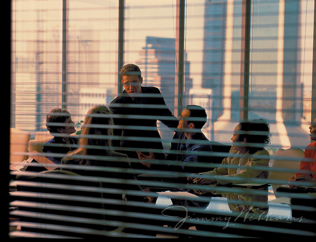 Employees meet in a board room to discuss the upcoming week at work