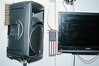 An American flag hangs between a speaker and a television while Ohio governor and Republican presidential candidate John Kasich speaks at a town hall campaign event at Raymond VFW Post 4479 in Raymond, New Hampshire, on Wed., Feb. 3, 2016.