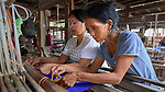 Zirtluangi (left) and Vanlalmuati weave cloth on a traditional loom in Kalay, a town in Myanmar.