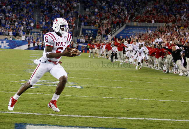 Kawaun Jakes runs to score WKU's final touchdown during overtime in the game against the University of Kentucky as fans and teammates cheer on in the background. Western Kentucky University won 32-31at Commonwealth Stadium on Saturday, Sept. 15, 2012. Photo by Latara Appleby | Staff