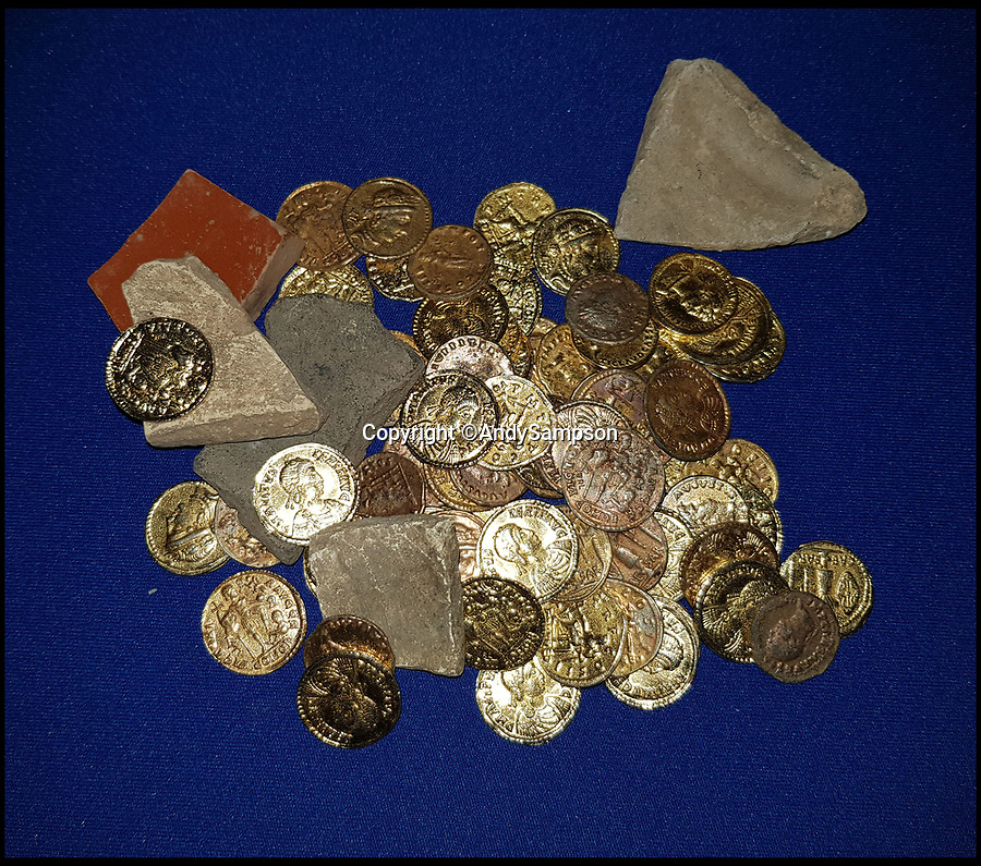 BNPS.co.uk (01202 558833)Pic: AndySampson/BNPS<br /> <br /> The 'golden' hoard and pottery that Andy and Paul dug up.<br /> <br /> Fools gold...Two hapless treasure hunters thought they had struck it rich when they found a hoard a gold coins - only to discover they were fakes buried for the TV comedy Detectorists.<br /> <br /> Metal detectorist Paul Adams began dancing around a field, crying out 'Roman gold! Roman gold!' when he stumbled upon a handful of ancient coins.<br /> <br /> Colleague Andy Sampson dashed across to help and to their astonishment within minutes they had unearthed 54 Roman gold coins, potentially worth £250,000.<br /> <br /> The pair spent 24 hours believing the treasure to be genuine and they even started thinking about what to blow their windfall on.<br /> <br /> But the next day an expert told them he feared the coins were fake before it was confirmed they had been left in a field by the film crew making the hit BBC series Detectorists.