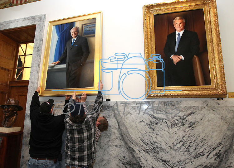 A state buildings and grounds crew hangs Gov. Jim Gibbons' portrait in the Capitol in Carson City, Nev. on Friday, Dec. 17, 2010. .Photo by Cathleen Allison