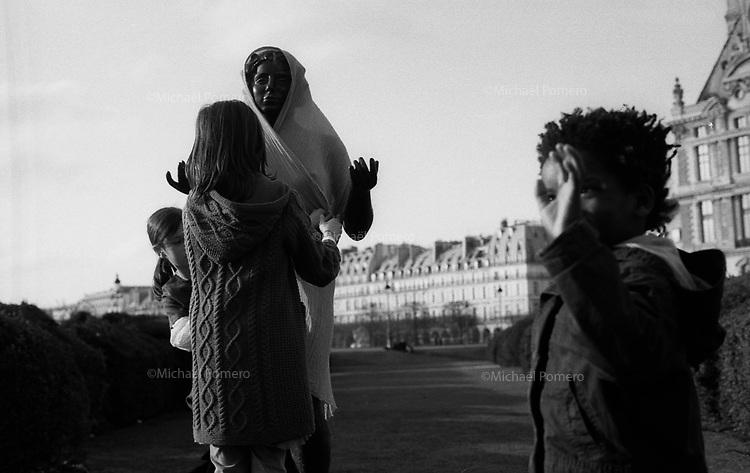 03.2010 Paris (&icirc;le de france)<br /> <br /> Enfant s'amusant a habiller une statue.<br /> <br /> Children having fun to dress a statue.