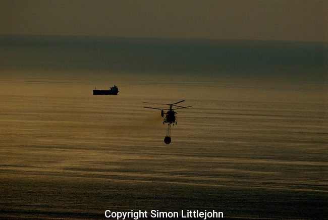 Twin rotor Kamov helicopter heading out to sea to refill water ballon to fight a forest fire on Spains Costa del Sol .