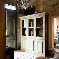 A white painted display cabinet stands in the hallway of a traditional house.