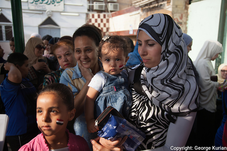 Polling station in Shubra, Cairo.<br /> <br /> Suha Omar, 28 accompanied by her daughters Rawda, 1, and Mariam 8, waits in line outside the booth.