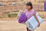 A Rohingya girl carries a tarp and blankets she received during a distribution of aid from several groups, including Dan Church Aid, in the Jamtoli Refugee Camp near Cox's Bazar, Bangladesh. Dan Church Aid is a member of the ACT Alliance.<br /> <br /> More than 600,000 Rohingya have fled government-sanctioned violence in Myanmar for safety in Bangladesh.