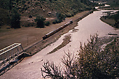 D&amp;RGW excursion train has just crossed steel truss bridge west of Juanita.  Ten Silverton cars plus a gondola.  Probably Rocky Mountain Railroad Club excursion of Memorial Day in either 1957 or 1958.<br /> D&amp;RGW  Juanita, CO  1957-1958