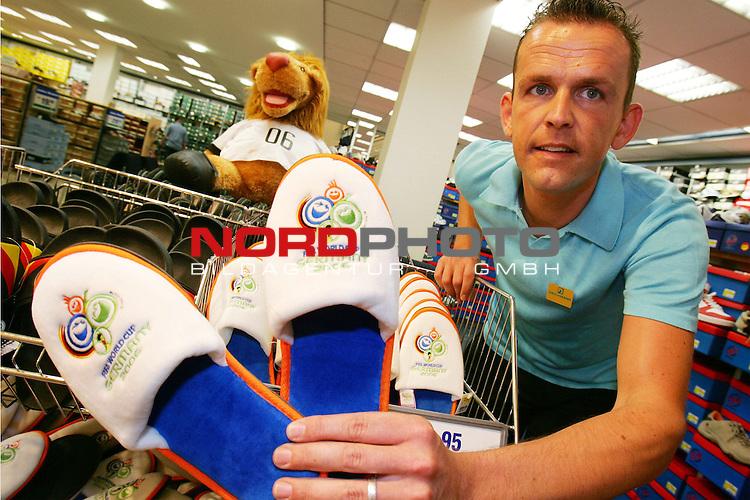WM Fuflball Fussball Weltmeisterschaft 2006, Fanartikel,  Schuhverk&permil;ufer Sascha Reitz (29 Jahre) bei Schuhhaus Deichmann in der Innenstadt Kassel pr&permil;sentiert Badeschuhe mit FIFA-2006-Logo f&cedil;r 2,95 Euro, desweiteren gibt es Badelatschen des DFB, Turn- und Straflenschuhe mit DFB- und FIFA-Logo in allen Deichmann-Filialen, Foto &copy; nordphoto *** Local Caption *** Foto ist honorarpflichtig! zzgl. gesetzl. MwSt.<br /> Belegexemplar erforderlich<br /> Adresse: nordphoto<br /> Georg-Reinke-Strasse 1<br /> 49377 Vechta
