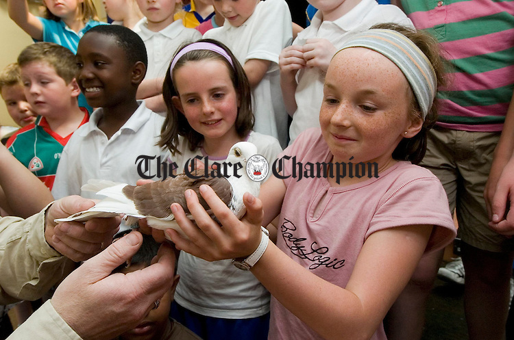 Nora Casey and Laoise O Malley get a chance to hold a bird during the visit of Banner Racing Pidgeon Club to the Ennis CBS. Photograph by John Kelly.