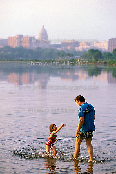 A parent and child play in the water at Bernie's Beach, one of several city parks, on Lake Monona Bay during a summer sunset.  In the background is the Wisconsin State Capitol building dome and downtown Madison, WI skyline..Photo © Jeff Miller 2000 - all rights reserved.www.jeffmillerphotography.com  ?  608-250-2374.Date:  2000    File#:   color slide
