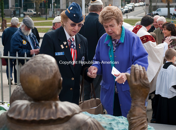 WATERBURY, CT--- -12075JS01--Gold Star Mother Mary Kight, left, and her friend Rita Volpe, right, look over the Father Thomas M. Conway statue following a Mass Monday at the Basilica of the Immaculate Conception in Waterbury. <br /> Jim Shannon Republican-American