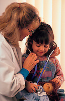 Female doctor helps her young female patient feel more comfortable by allowing the child to wear her stethoscope to pretend to listen to the doll's heart.