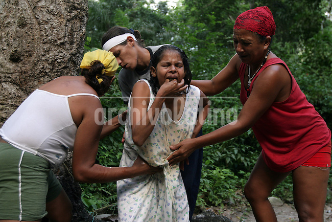 Under the command of a santeria pristess (in red) 21-year-old Andrea Gómez push a cigar into her mouth to induce vomity as the start of rite to heal her psychological pregnancyy  in the Sorte Mountains in Yaracuy State, Venezuela