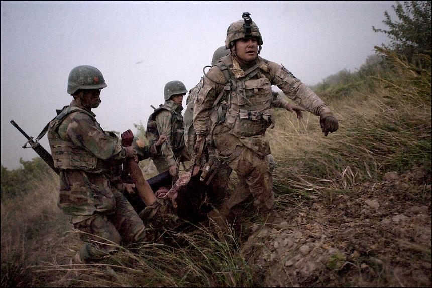 "U.S. soldiers from the 1st Battalion, 320th Field Artillery Regiment, near COB Terra Nova, Arghandab valley, Kandahar, Afghanistan, carry an ANA soldier who was wounded on patrol to a ""Shadow Dustoff"" helicopter, September 18th, 2010. The soldier was a double amputee from a pressure plate IED."