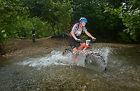 NWA Democrat-Gazette/BEN GOFF @NWABENGOFF<br /> Mathew Daughrity, a cat 3 men age 13-14 racer from Bella Vista, fords a creek Sunday, July 16, 2017, during cross country races on the final day of the 19th annual Fat Tire Festival at Lake Leatherwood City Park in Eureka Springs.