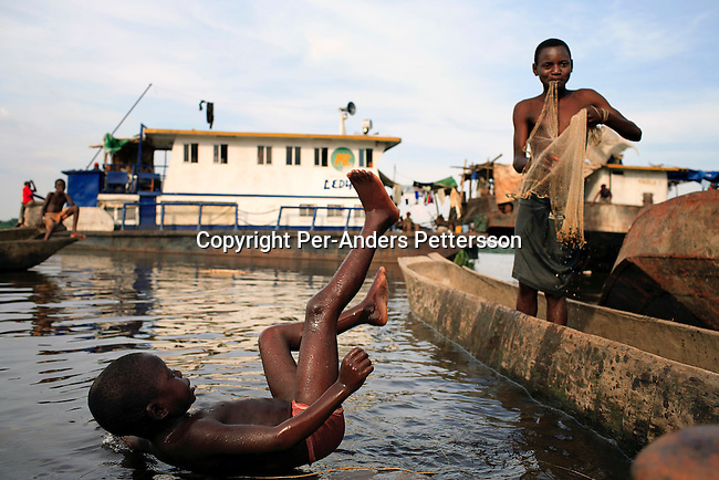 LUKUTU, DEMOCRATIC REPUBLIC OF CONGO MARCH 16: Unidentified boys play in the water on March 16, 2006 in Lukutu port, Congo, DRC. Many boats stop in this little village, about 1500 kilometers from Kinshasa, the capital. Congo River is a lifeline for millions of people, who depend on it for transport and trade. The journey from Kisangani to Kinshasa is about 1750 kilometers, and takes from 3-7 weeks on the river, depending on the boat. During the Mobuto era, big boats run by the state company ONATRA dominated the traffic on the river. These boats had cabins and restaurants etc. All the boats are now private and are mainly barges that transport goods. The crews sell tickets to passengers who travel in very bad conditions, mixing passengers with animals, goods and only about two toilets for five hundred passengers. The conditions on the boats often resemble conditions in a refugee camp. Congo is planning to hold general elections by July 2006, the first democratic elections in forty years..(Photo by Per-Anders Pettersson/Getty Images).