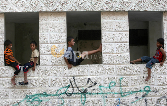 Palestinian children play outside their homes in Rafah refugee camp, southern Gaza Strip, during Muslims fasting month of Ramadan, July 29, 2013. Ramadan is the holiest month in the Muslim calendar, during which people refrain from eating, drinking and smoking from sunrise to sunset. Photo by Eyad Al Baba