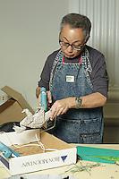OrigamiUSA artists preparing the models and designing the Holiday Tree at the American Museum of Natural History. Talo Kawasaki securing the models to bases.