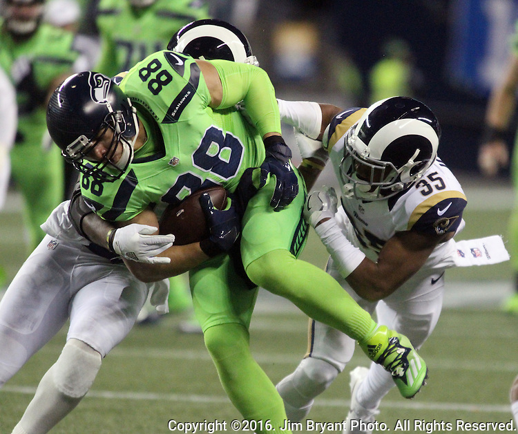 Seattle Seahawks tight end Jimmy Graham (88) fights through the tackles of Los Angeles Rams defensive back Michael Jordan (35) and Los Angeles Rams defensive back Cody Davis (38) after catching a 31-yard pass from quarterback Russell Wilson to set up a 1-yard touchdown at CenturyLink Field in Seattle, Washington on December 15, 2016.  The Seahawks beat the Rams 24-3.   ©2016. Jim Bryant Photo. All Rights Reserved