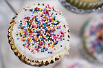 Decorated cupcakes in a cup cake holder close ups sprinkled with frosting