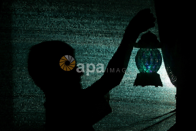 A Palestinian boy is seen behind a curtain holding a lantern behind on the third day of the Muslim fasting month of Ramadan, in Rafah in the southern Gaza Strip, on July 1, 2014. Muslims around the world celebrate Ramadan, the holiest month in the Islamic calendar, in which they abstain from eating, drinking and conducting sexual relations from sunrise to sunset. Photo by Eyad Al Baba