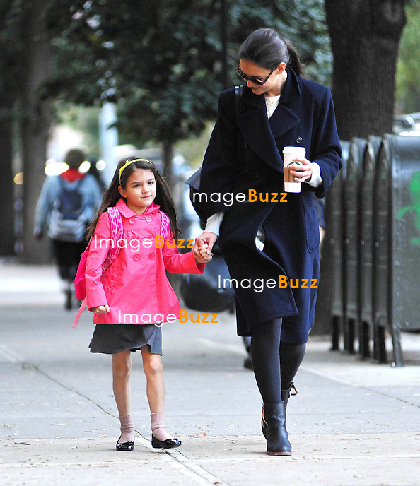 Katie Holmes holds her daughter Suri's hand as they leave their apartment building and head to school on Monday morning October 22, in New York City..The 6-year-old daughter of Katie and Tom Cruise looked happy as can be in her pink jacket..New York City, October 22, 2012.