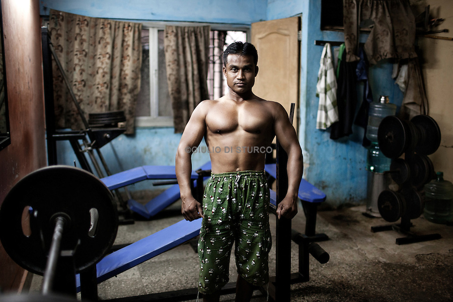 """INDIA, MUMBAI 2014<br />Iqbal training in the only gym present in Lallubhai compound.<br />Mumbai """"slum rehabilitation"""" project forced people to move to places like Lallubhai Compound in Mankhurd: <br /> 100 building central cluster rises ominously, each building separated from the other by a small corridor full of garbage,.Welcome to Mumbai's slum resettlement housing projects, the future of the big metropolis, Vertical Slums @Giuliodisturco"""