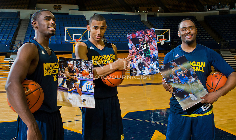 Michigan basketball players Tim Hardaway, Jr., left, Jon Horford, center, and Jordan Dumars, right, hold up portraits of their NBA fathers after a team practice, Thursday, Nov. 11, 2010, at Crisler Arena in Ann Arbor, Mich. Hardaway, Jr. is the son of former Miami Heat All-star Tim Hardaway, Dumars is the son of former Detroit Pistons All-star and current President of Pistons Basketball Joe Dumars, and Horford is the son of former Milwaukee Bucks' Tito Horford and brother to the Atlanta Hawks' Al Horford. (AP Photo/Tony Ding)