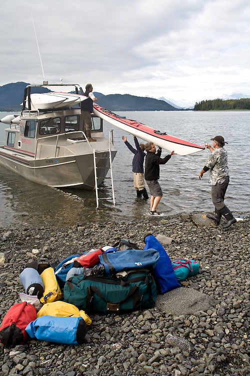 Alaska, Prince William Sound, Sea kayakers, Lazy Otter boat shuttle, USA, Sea kayakers unloading camping gear, kayaks,