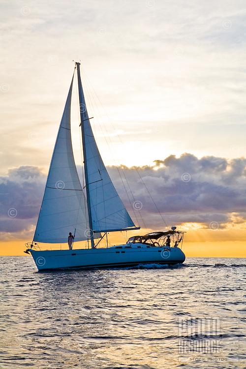 Cruising sailboat at sunset off the west coast of Oahu, Hawaii
