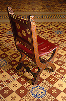 An embossed red-leather carved chair stands in isolation against the backdrop of the neo-Gothic ceramic tiled floor of the House of Lords
