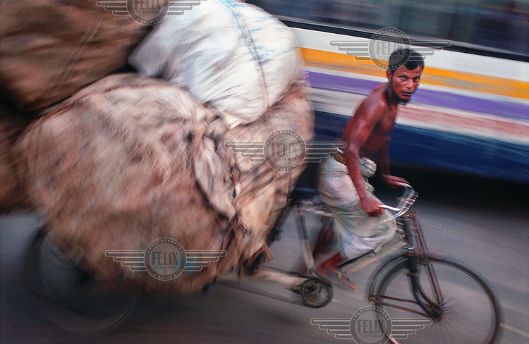Rickshaw with a heavy load. Dhaka is a city of over 600,000 rickshaws. The drivers - rickshaw wallahs - are mostly migrants from the countryside.