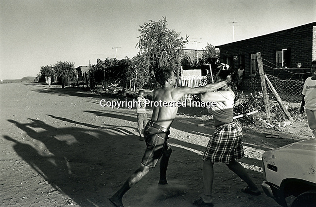 disiabu00034.Social Issues. Abuse. A domestic fight, in the open on Sultana Road, in Loisevale, Upington on Febrary 9, 2002 in Loisevale, Upington. Baby Thsepang was raped in October-2001 in Loisevale ner Upington, South Africa. Loisvale is a poor and destitute colored/black township where unemployment is very high and a high number of abuse and alcohol cases..©Per-Anders Pettersson/iAfrika Photos