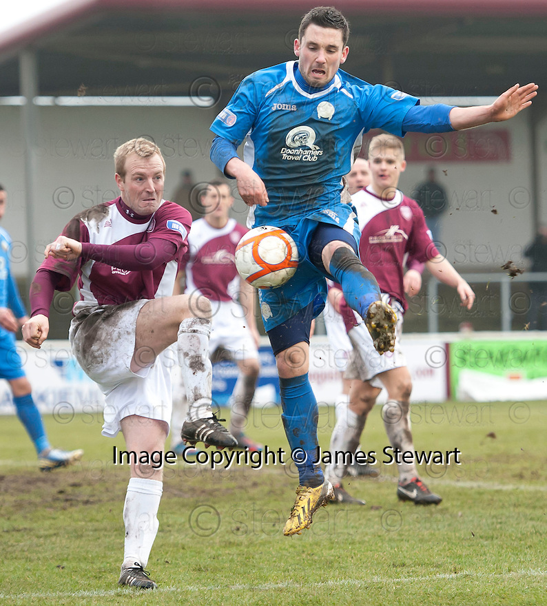 Queen of the South's Nicky Clark blocks Arbroath's Brian Kerr's clearance.