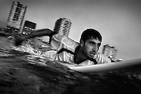 20 year old surfer Mohammed Shamalak paddles out into the Mediterreanean Sea off Gaza City.