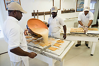 People watch as Daniel Ferguson, 50, (from left), Maurice Scott, 28, and Davian Miller, 24,  make fudge at Murdick's Fudge in Edgartown, Martha's Vineyard, Massachusetts, USA, on Tues., July 25, 2017.  Ferguson is from Jamaica and has an H2B seasonal foreign worker visa. He says 2017 is his sixth summer season working in the fudge shop. During off-months, he returns to Jamaica where he can be with family and escape the cold weather. Miller has worked here for two seasons, and Scott for four seasons. Most of the shop's workers are seasonal foreign workers. Other companies on Martha's Vineyard and around the US had difficulty obtaining H2B visas, but Murdick's Fudge received all it requested.