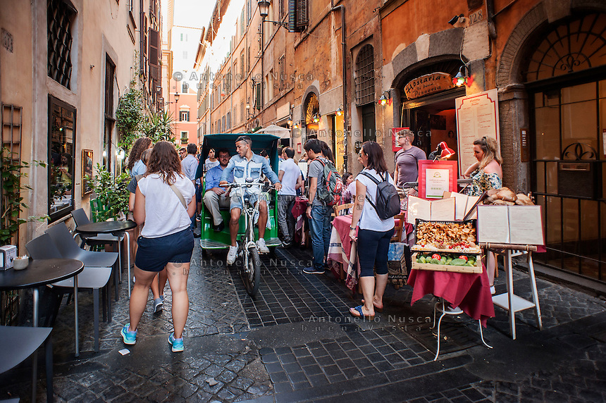 Un risci&ograve; ppassa tra i tavolini dei ristoranti in un vicolo del centro storico adiacente al Pantheon.<br /> A pedicab scrape through tourists in downtown