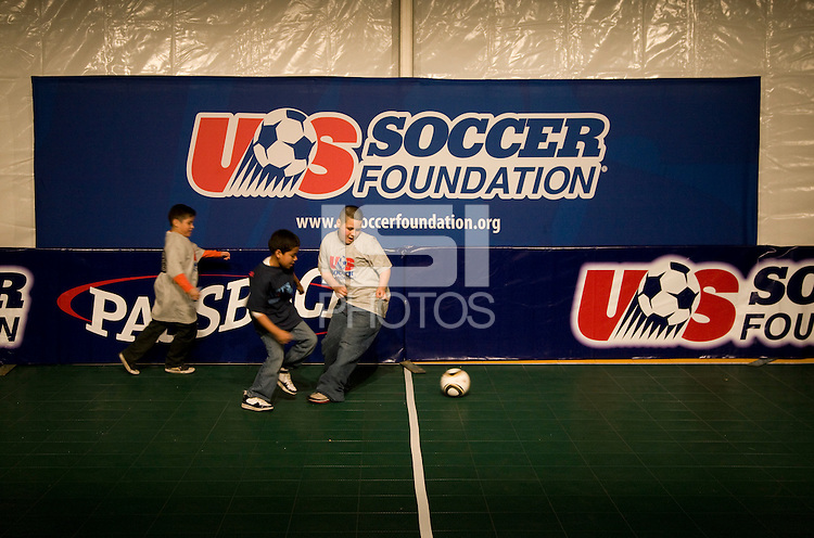 Local children sprint down the field during a US Soccer Foundation clinic held at City Center in Washington, DC.