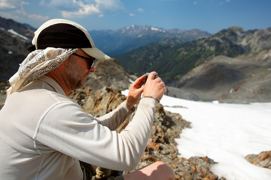 Backpacker taking photo in mountains, Bailey Range Traverse, Olympic Mountains, Washington