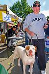 Tall senior man walking bulldog and wearing Army sweatshirt and Vietnam Veteran cap at Merrick Street Fair in Merrick; New York; USA; on October 22; 2011; editorial