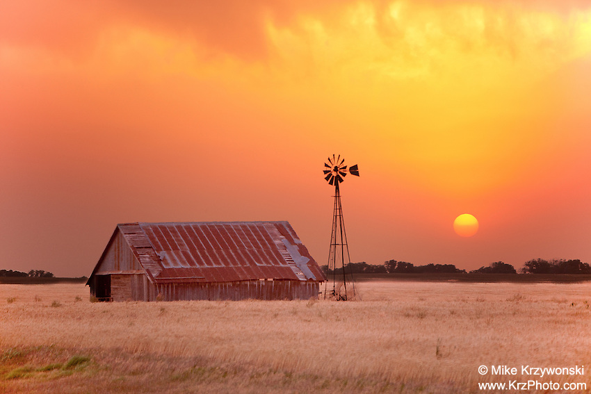 Golden orange sunset behind an abandoned barn & windmill in Oklahoma