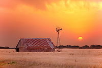 Golden orange sunset behind an abandoned barn & windmill in Oklahoma