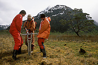 Dr. Harald Biester and students Oscar Baeza and Sascha Birkenstock push a sharpened sleeve into a bog at the foot of the Gran Campo Nevado ice field to remove a core from its 10,000-year-old peat. The region's many bogs trap pollens and chemicals dispersed through the air and water. Peat cores take scientists back thousands of years with each foot of depth.