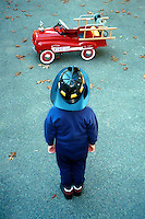 Boy with fireman hat looking at a toy fire engine.