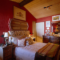 A pair of salvaged wooden shutters decorates the wall behind the upholstered headboard of this queen sized bed