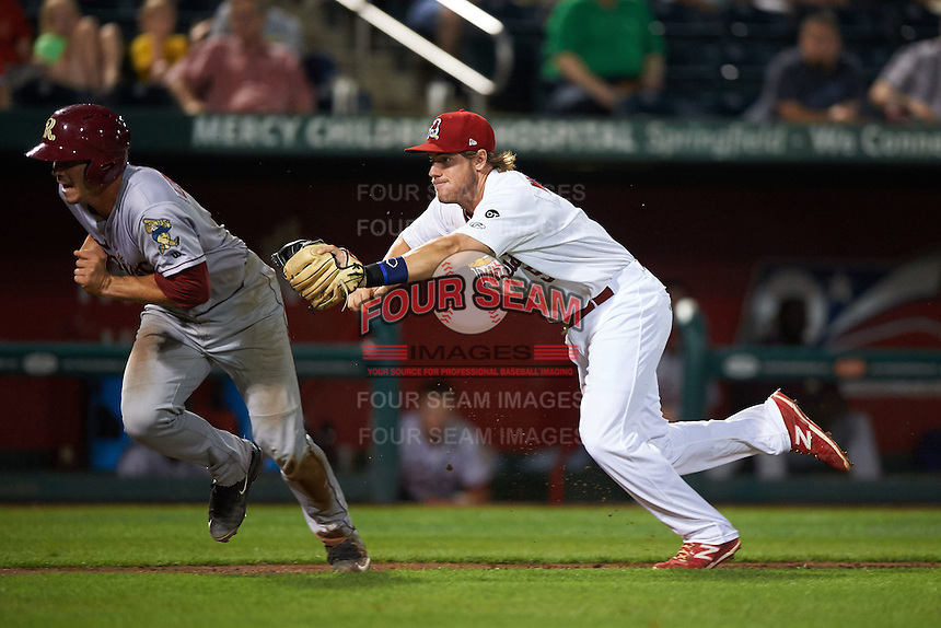 Springfield Cardinals third baseman Patrick Wisdom (5) makes a diving tag on Patrick Cantwell (3) during a game against the Frisco RoughRiders  on June 4, 2015 at Hammons Field in Springfield, Missouri.  Frisco defeated Springfield 8-7.  (Mike Janes/Four Seam Images)