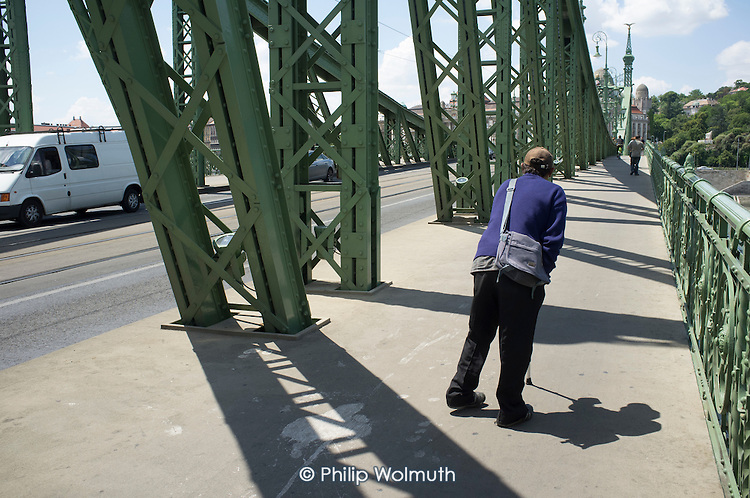 A disabled man with a walking stick begging on the Lanchid bridge over the river Danube, Budapest.
